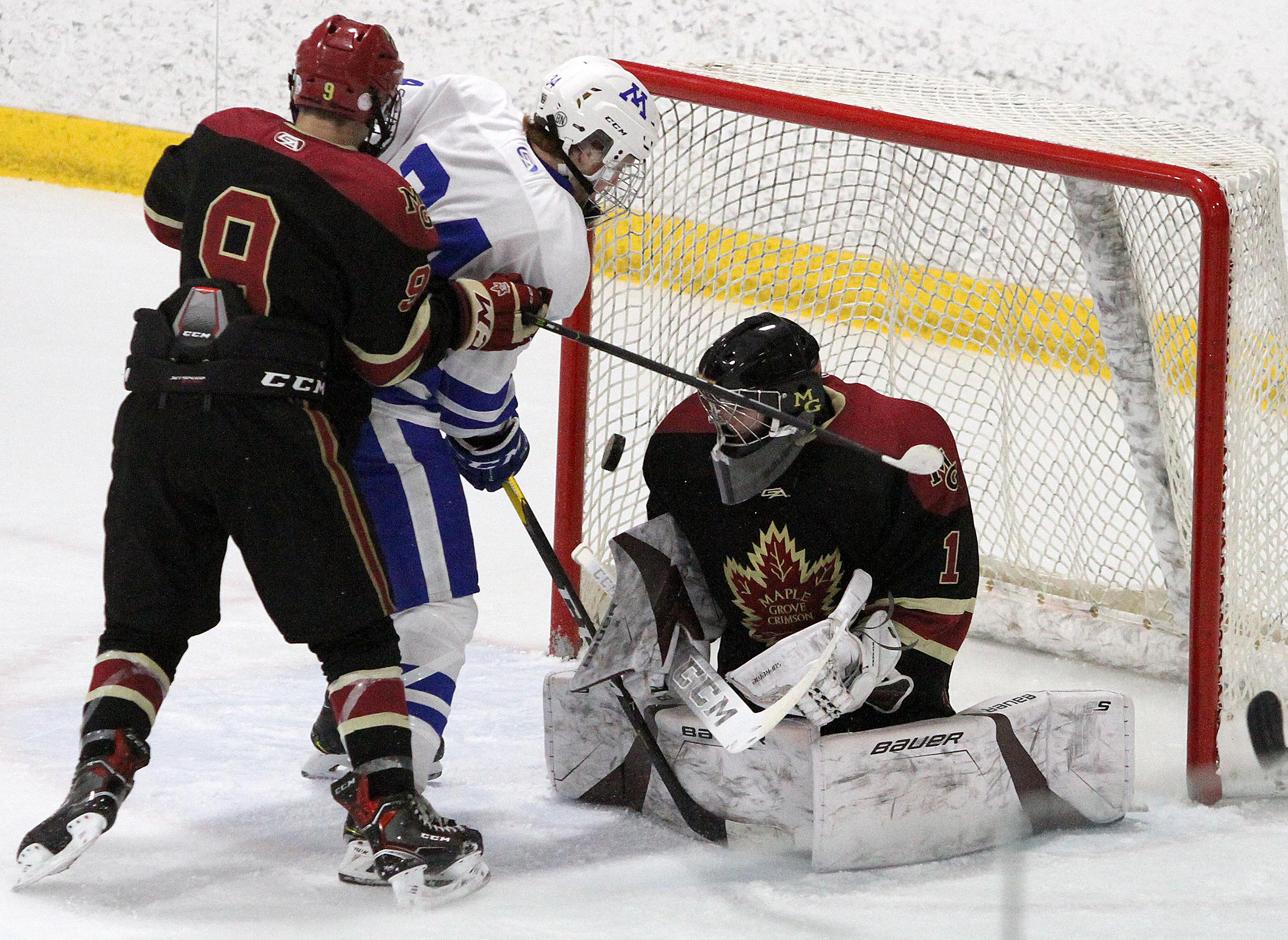 Minnetonka forward Teddy Lagerback battles for the puck in the crease between Maple Grove goalie Jack Wieneke and center Kyle Kukkonen during the third period of Friday night's game at The Tradition in the Park Classic. Photo by Drew Herron, SportsEngine