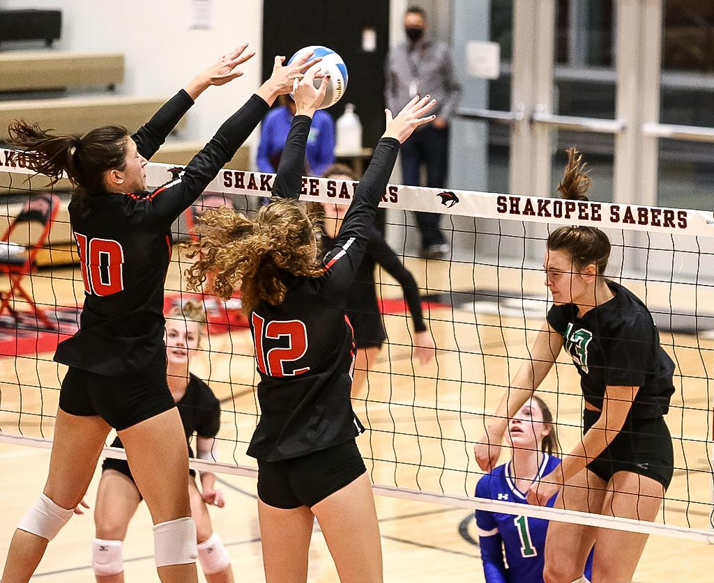 Shakopee's Ary Forsberg (10) and Maddie Meyer (12) team up at the net for a block in the first set. The Sabers took down the Wildcats in five sets on Wednesday night. Photo by Cheryl A. Myers, SportsEngine