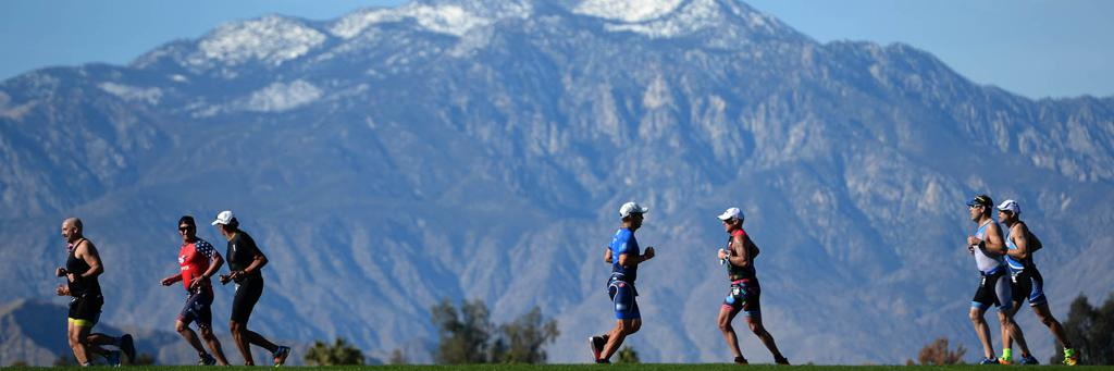 Triathletes running, mountains in background, IRONMAN Indian Wells 70.3