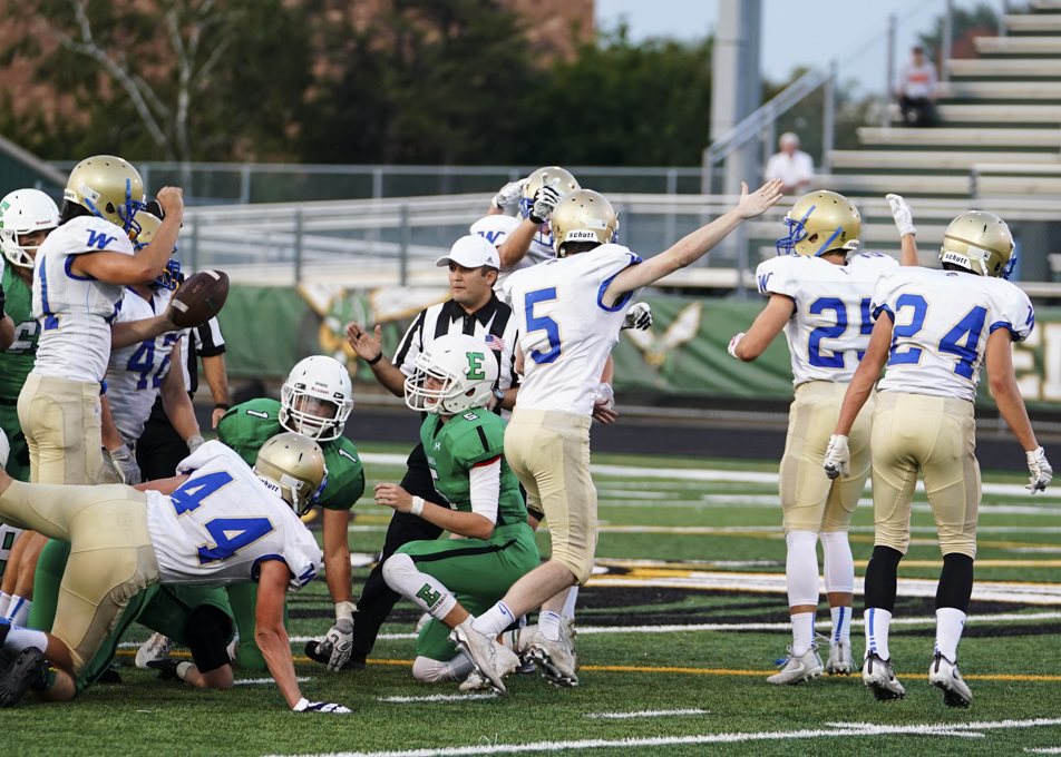 Junior defensive back Jacob Beeninga (5) and the Trojans confirming a fumble recovery in the first half of a 29-0 loss to Edina. Photo by Travis Ellison, SportsEngine