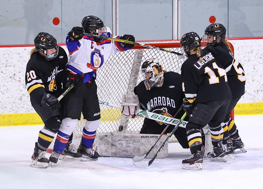 Gentry Academy's Angelina Ruiz gets the puck up and over the pad of Warroad goaltender Kendra Nordick. Ruiz's goal put the Stars up by two goals in the second period. Photo by Cheryl A. Myers, SportsEngine