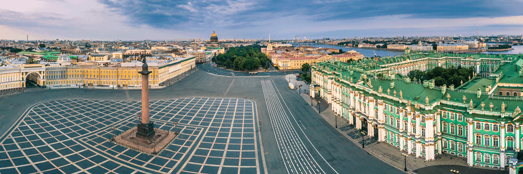 Wide angle image of green-and-white Winter Palace and Alexander Column on Palace Square next to Neva River and other buildings of St. Petersburg, Russia