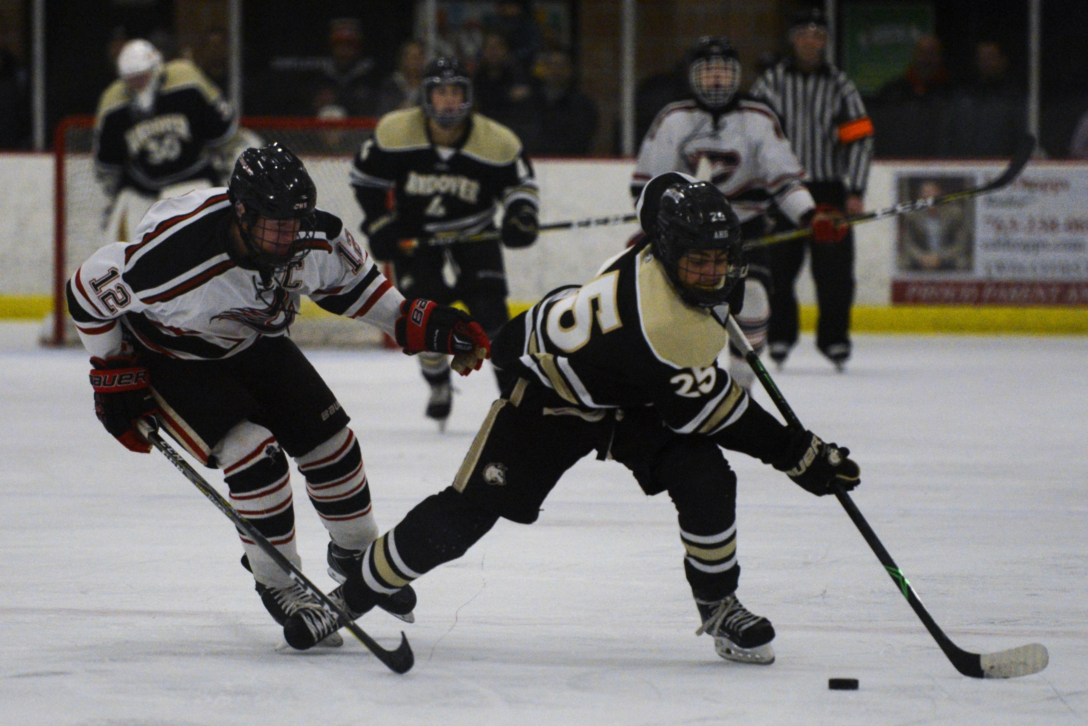 Andover forward Charlie Schoen (25) skates up the ice against Centennial defender Luke Arends (12). Schoen scored his 18th goal of the season in the 2-0 win. Photo by Carter Jones, SportsEngine