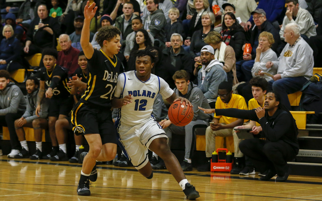 Minneapolis North guard Nasir El-Amin drives for the basket around DeLaSalle's Andrew Irvin on Tuesday night. The Polars fell to the Islanders 66-57. Photo by Jeff Lawler, SportsEngine