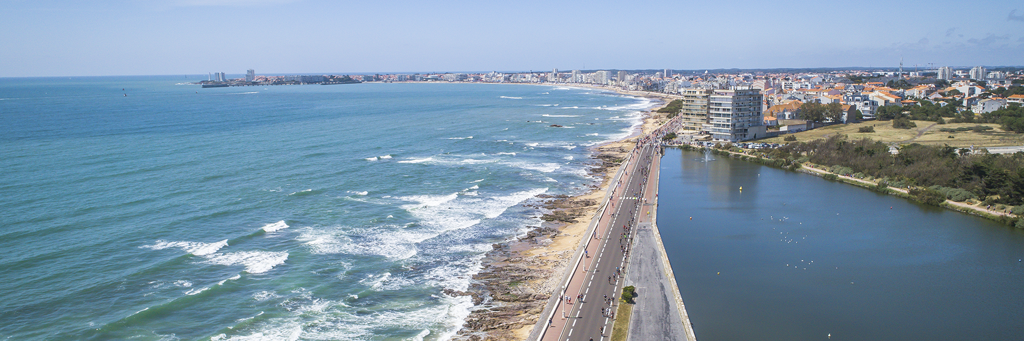View of the Atlantic Ocean and athletes running on the promenade along the Tanchet lake at IRONMAN 70.3 Les Sables d'Olonne