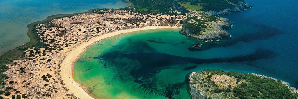 Voidokilia Beach with dark blue and green shining water and semicircular strip of dunes in the Mediterranean area at Costa Navarino Greece