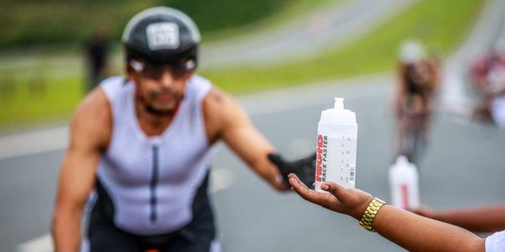 Triathlete on bike being handed water