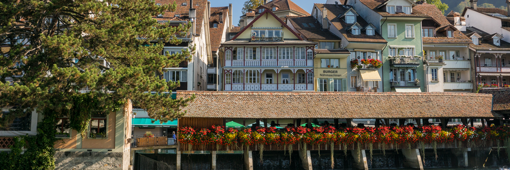 Old town of Thun Switzerland with small houses and lots of flowers built next to each other along Aare river