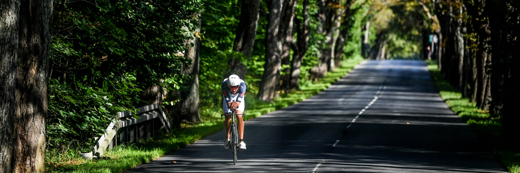 Single athlete biking through a shady avenue of trees at IRONMAN 70.3 Gdynia