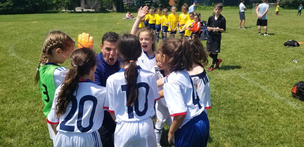 coach with excited group of female players in a huddle