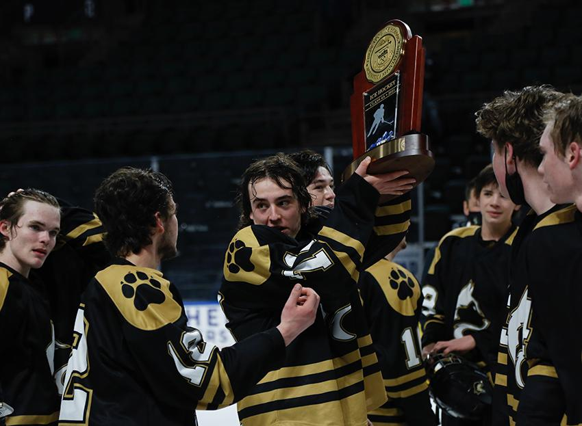 Jensen Rawlings shares the championship trophy with his teammates on March 18. With their 5-4 overtime defeat of Crested Butte, the Huskies were the inaugural winners of the state's Class 4A ice hockey title. Photo by Steven Robinson, SportsEngine