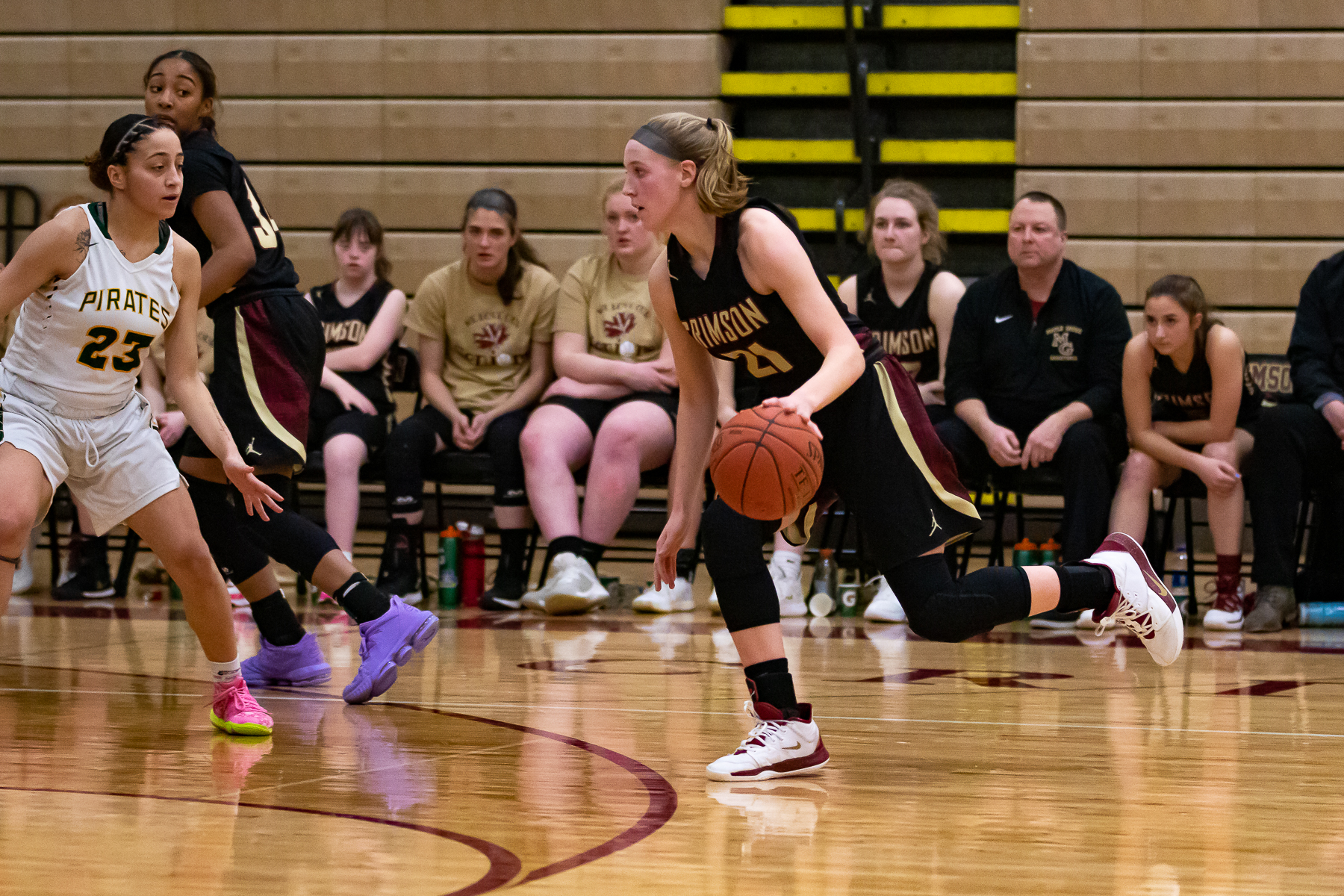 Maple Grove senior Abby Schulte (21) drives to the basket against Park Center's Kayla Cox (23). Schulte's 22 points led the Crimson in their 69-65 loss to the Pirates at Maple Grove High School. Photo by Gary Mukai, SportsEngine