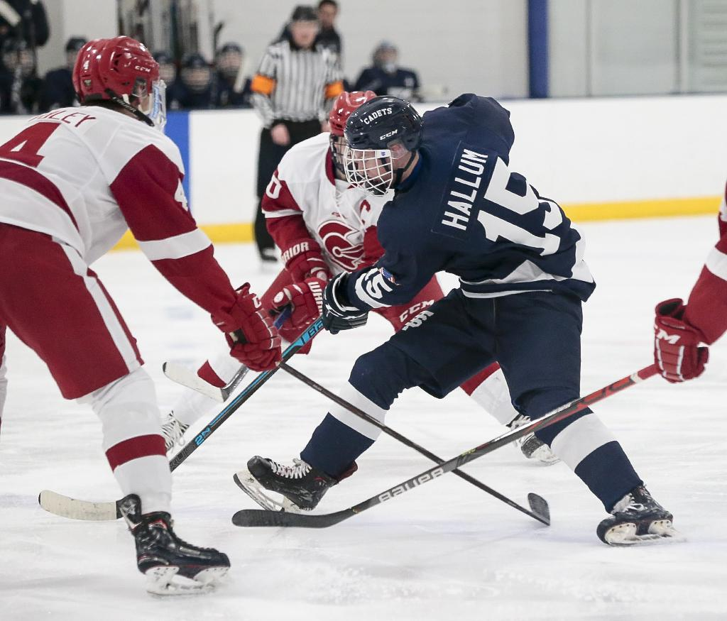St. Thomas Academy's Jackson Hallum (15) carries the puck through a trio of Benilde-St. Margaret defenders. Hallum tallied two assists in the Cadets' 3-2 win over the Red Knights on Wednesday night. Photo by Cheryl A. Myers, SportsEngine