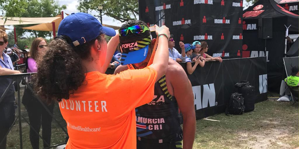 Volunteer putting medal around finisher's neck