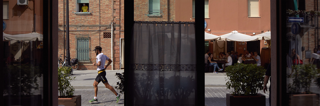Athlete running through the heart of Cervia seen through a store at IRONMAN Italy Emilia-Romagna