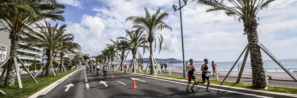 Athletes running on the Promenade de Anglais next to the beach,palm trees and Mediterranean Sea in Nice France