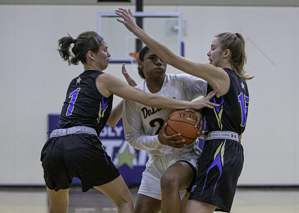 DeLaSalle's Nurjei Weems (22) split Holy Angels defenders Francesca Vascellaro (left) and Becky Little for two of her 22 points. Photo by Mark Hvidsten, SportsEngine