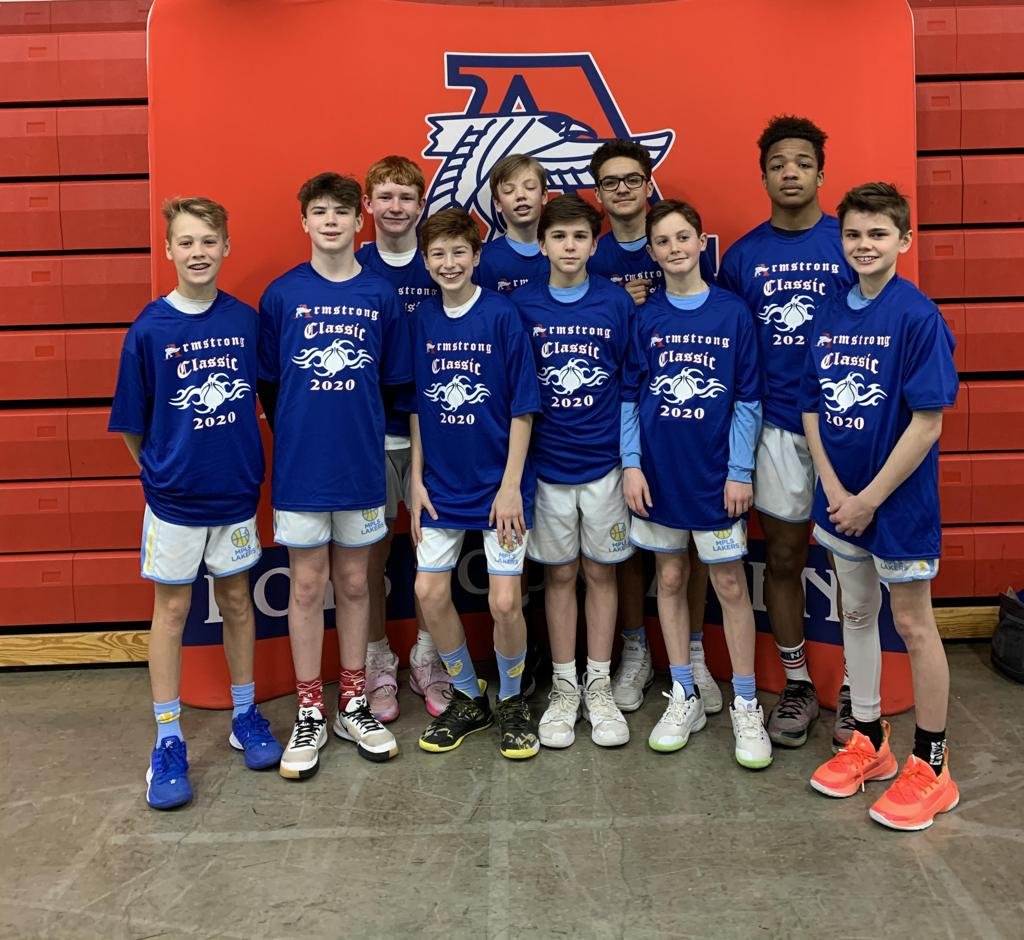 Mpls Lakers Youth Traveling Basketball Program Inc Boys 7th Grade Gold pose with their T-Shirts after becoming the Champions at the Armstrong Classic tournament in Robbinsdale, MN