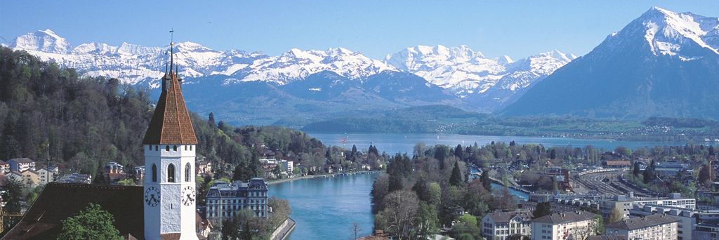 Top of a church and views of Aare river and majestic snow covered mountains in Thun Switzerland