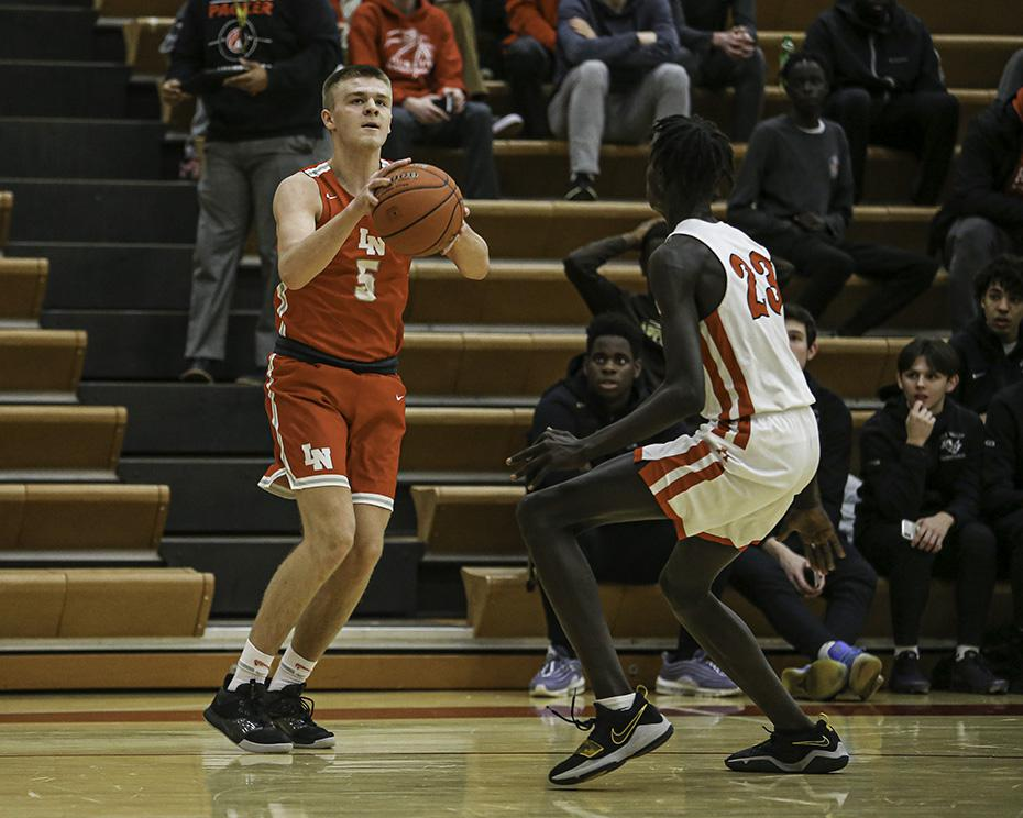Lakeville North's Noah Frechette (5) set up for a three-point shot in the first half. Frechette scored all 20 of his points in the first half as the Panthers took an early lead. Photo by Mark Hvidsten, SportsEngine