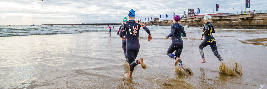IRONMAN 70.3 South Africa athletes running into the Indian Ocean at Orient Beach next to a pier in East London, Buffalo City