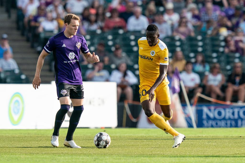 Nashville SC's Bolu Akinyode takes on Louisville City FC defender