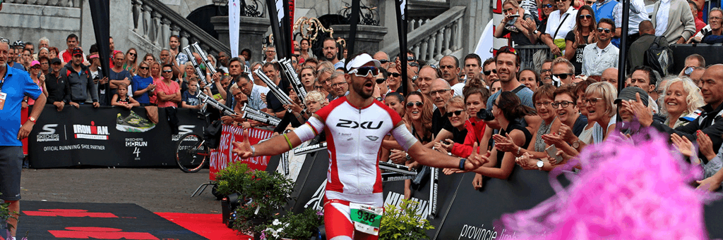 Athlete is entering the finish line on de Markt in the center of Maastricht, while many spectators are watching and cheering at 5150 Maastricht-Limburg