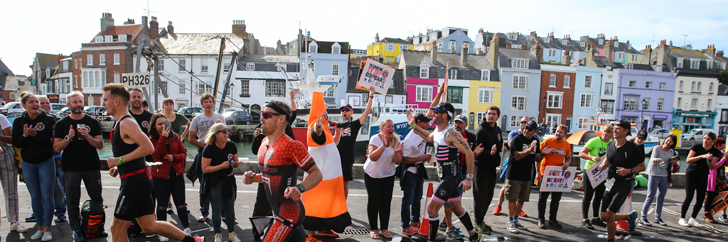 IRONMAN 70.3 Weymouth athletes running along Weymouth's esplanade to the Finish Line with massive people watching and loudly cheering them on