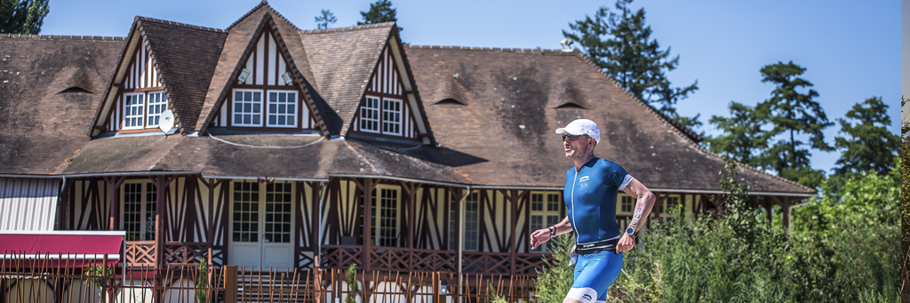 Athlete running along Lake Allier and passing by an old styled and brown white covered house at IRONMAN 70.3 Vichy