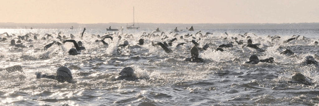 Lots of Kalmar Mini Tri athletes swimming at Kattrumpan beach at sunrise