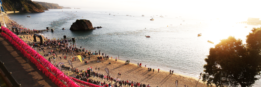 IRONMAN Wales swim course at famous Tenby North Beach with viewing the Goscar Rock, the sea and participants and supporters at sunrise