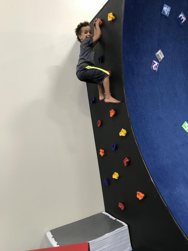 Child climbing the rock wall at a ninja clinic