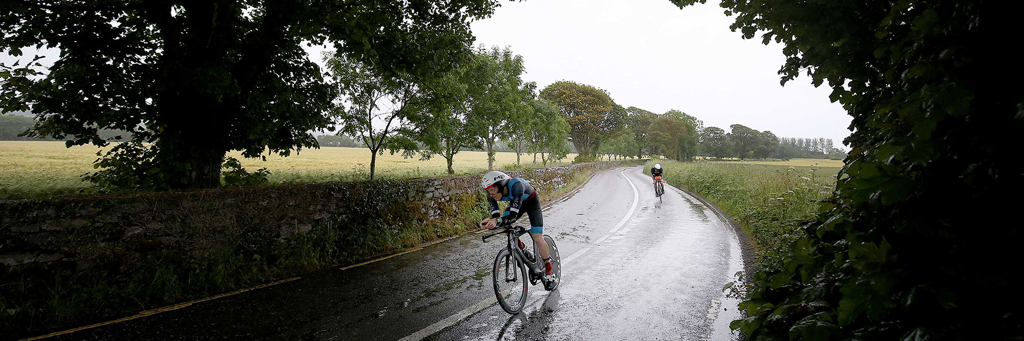 IRONMAN Ireland Cork athletes biking on a lane surrounded by trees and fields on a rainy day