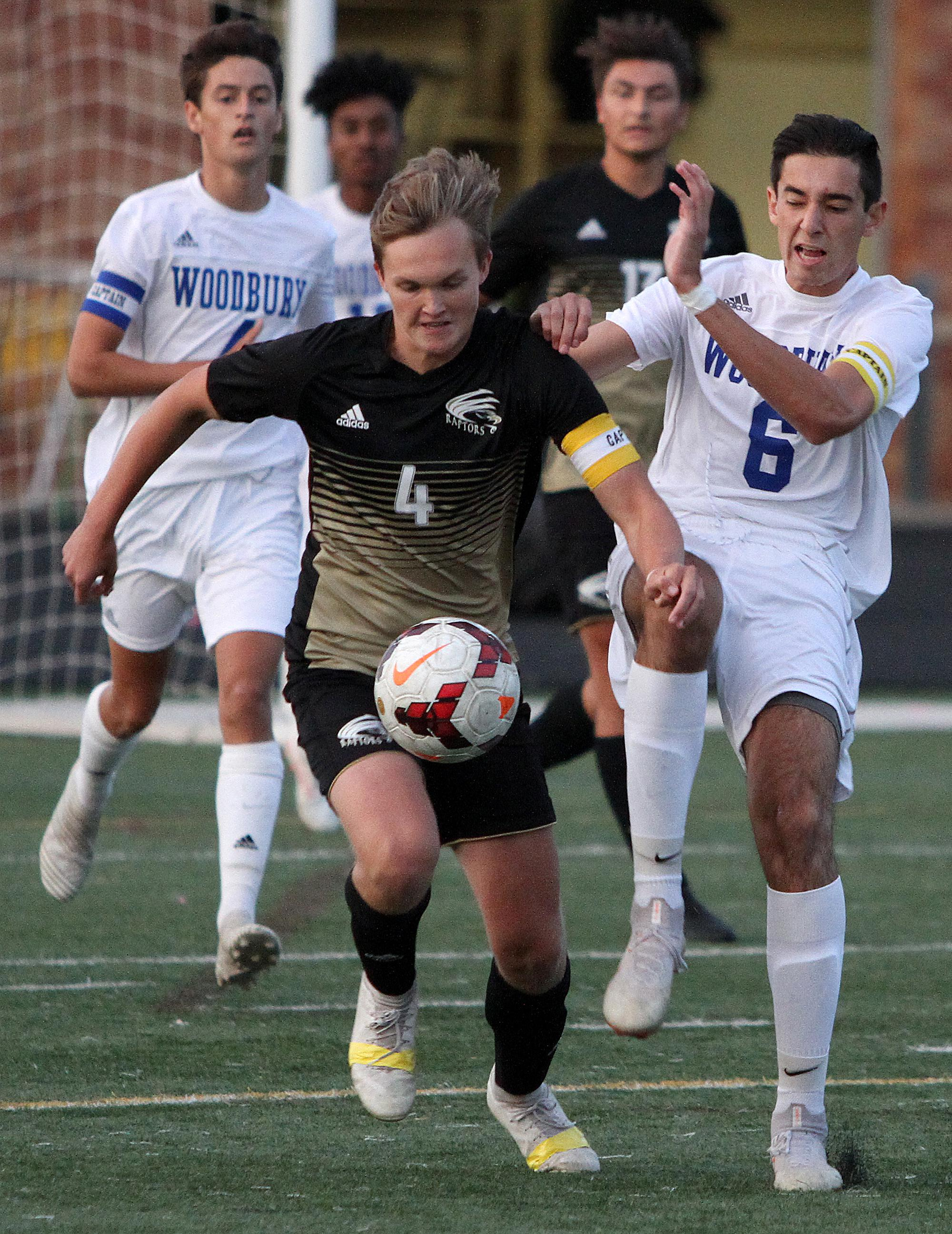 Senior captains and midfielders Drew Kansas (East Ridge) and Josh Miller (Woodbury) chase down the ball. East Ridge scored twice in the second half to topple Woodbury 2-1. Photo by Drew Herron, SportsEngine