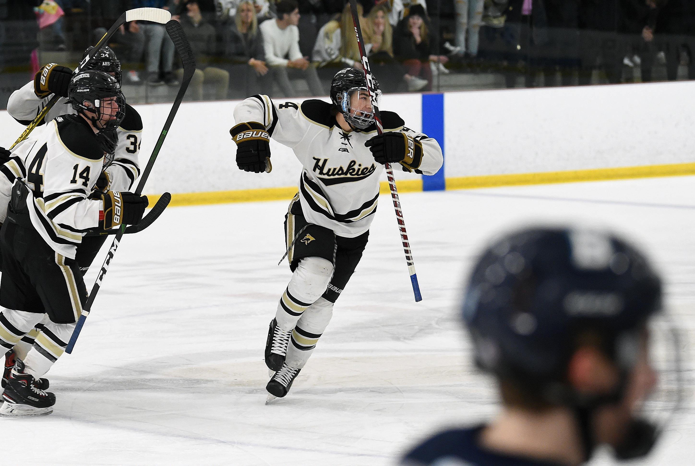 Andover defenseman Mitchell Wolfe, right, celebrates after scoring a second-period goal in the Huskies' 3-0 victory over Blaine on Saturday. Photo by Loren Nelson, LegacyHockeyPhotography.com