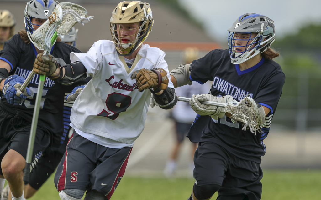 Lakeville South junior Peter Carlson tries to maintain control of the ball under the defensive pressure of Owatonna's Mitchell Wiese. Carlson and the Cougars prevailed 11-6 over the Huskies Saturday night in Lakeville. Photo by Jeff Lawler, SportsEngine
