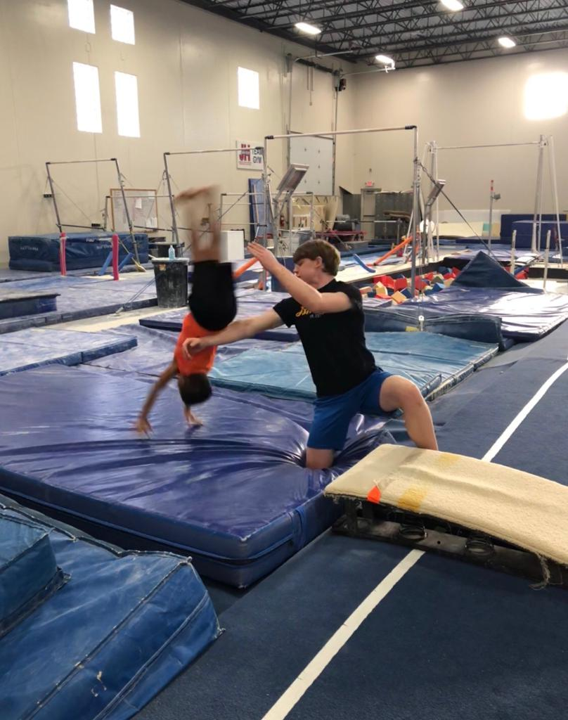Coach spotting child at back handspring skill clinic