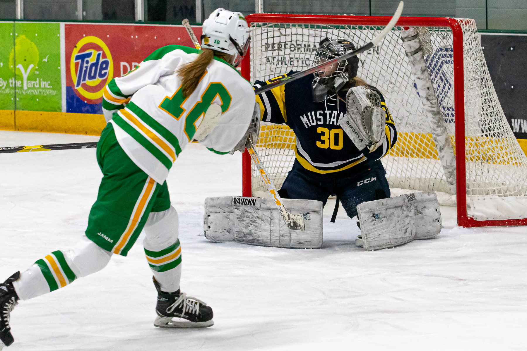 Edina forward Hannah Chorske fires a shot over the shoulder of Breck goalie Sarah Peterson in the first period. Chorske had four points in the Hornets' 6-1 defeat of the Mustangs Tuesday night in Edina. Photo by Gary Mukai, SportsEngine