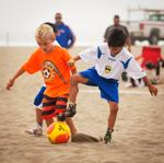 Two young kids play beach soccer in the Pro-Am Beach Soccer Youth Academy
