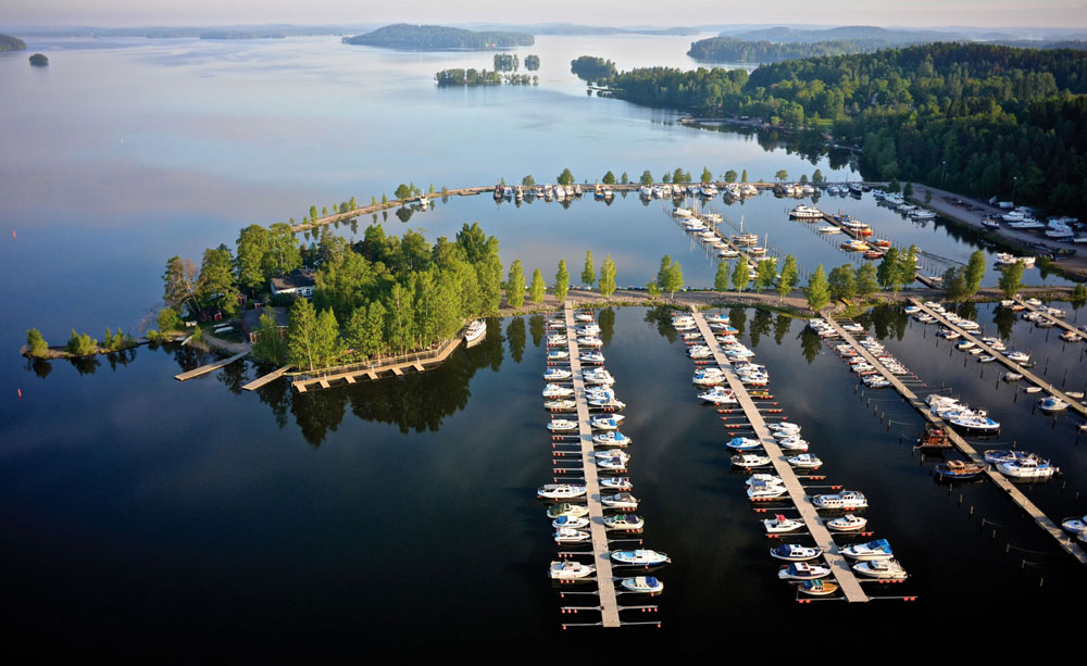 Bird's eye view of boats on docks and some small islands covered with trees in a beautiful lake in Lahti, Finland