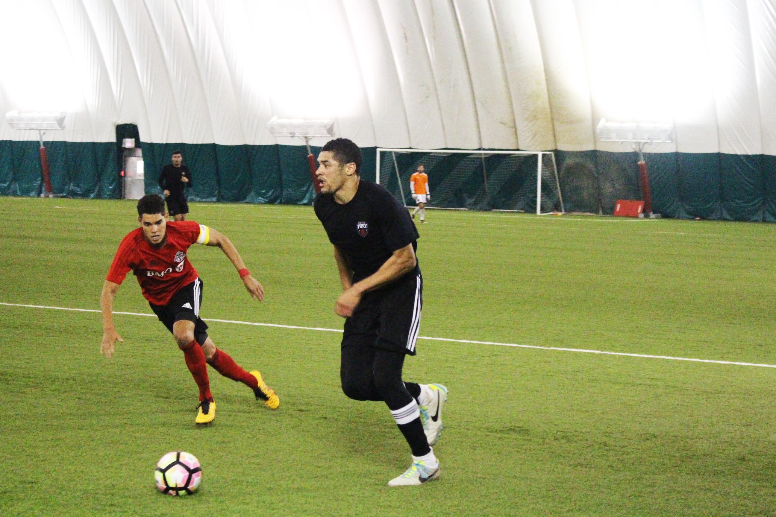 Onua Obasi, with the ball, looking for an option, with a Toronto defender near him