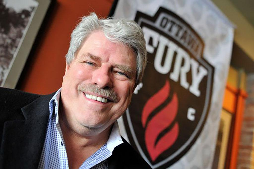 John Pugh smiling with a Fury FC logo in the background
