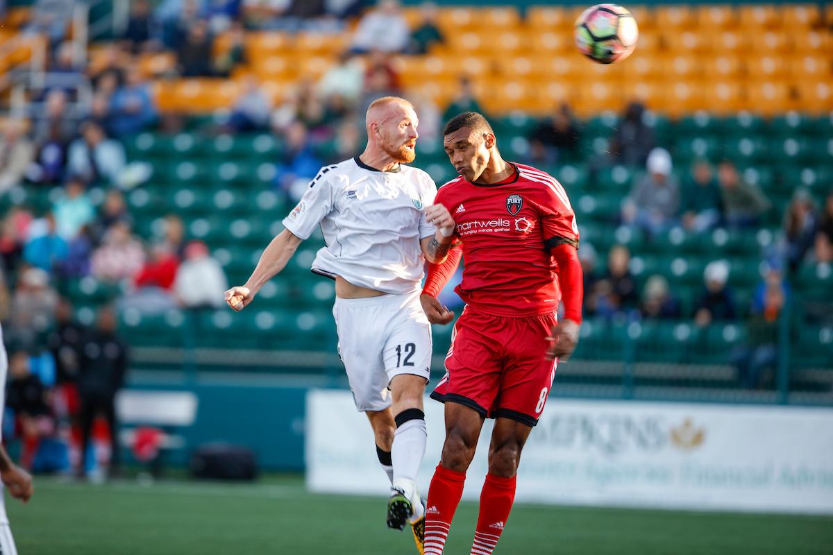 Steevan Dos Santos in the air, jumping to head a ball against a Rochester Rhinos' player