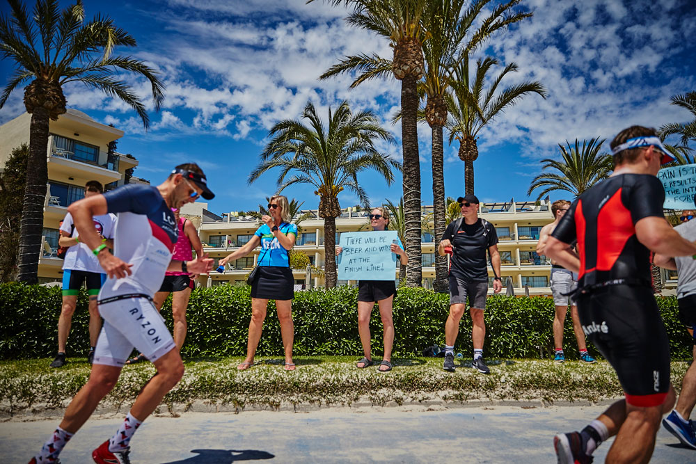Athletes running past supporters who are holding up posters at IRONMAN Mallorca